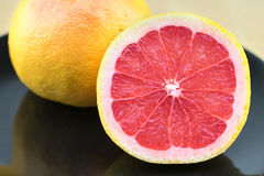 Fresh red grapefruit on the black plate. Royalty Free Stock Photos