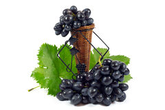 Fresh Red Grapes with Green Leaves in Wicker Basket Isolated on White Royalty Free Stock Image