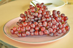 Fresh red grapes. Red no seed graves in clean plate Stock Image