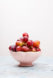 Fresh red grapes in a pink bowl on marble table. Sideview of fresh ripe red grapes in a pink bowl Royalty Free Stock Image