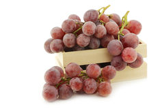 Fresh red grapes on the vine in a wooden crate Stock Photos