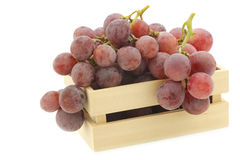 Fresh red grapes on the vine in a wooden crate Stock Image