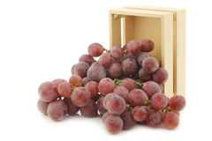 Fresh red grapes on the vine in a wooden crate Royalty Free Stock Image