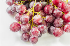 Fresh red grapes on white dish and wooden table. Royalty Free Stock Photo