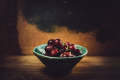 Fresh red grapes. On wooden background in ceramic bowl Royalty Free Stock Image