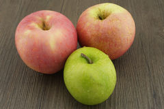 Fresh red and green apples on dark brown wood Stock Images