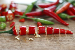 Fresh red and green chilli and chopped fresh red and green chilli on wooden chopping block. Stock Photography