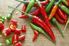 Fresh red and green chilli and chopped fresh red and green chilli on wooden chopping block. Stock Image