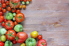 Fresh red and green tomatoes on a table at the left, on the righ. A blank space for the text Stock Photo