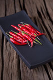 Fresh red hot chili peppers on dark plate over old wooden textur. Ed background Royalty Free Stock Photo
