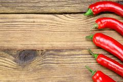 Fresh Red Hot Chili Peppers And Tomatoes. Fresh Red Hot Chili Peppers On The Rustic Wood Kitchen Table. Background With Copy Space Stock Photography
