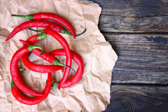 Fresh red hot chili peppers on an vintage wooden table Stock Images