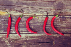 Fresh red hot chili peppers on an vintage wooden table. Royalty Free Stock Images
