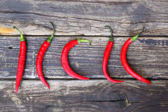 Fresh red hot chili peppers on an vintage wooden table. Royalty Free Stock Photos