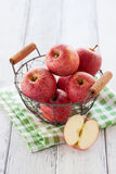 Fresh red juicy apples in a basket on a green textile on a wooden background Royalty Free Stock Image