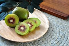 Fresh Red Kiwifruit on Wooden Plate. Close up red kiwifruit on wooden plate with space for text royalty free stock images