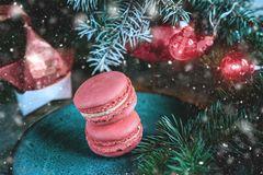 Fresh red macaroons at the Christmas table with the garland on the Christmas tree branches. Copy the place. Snow. The horizontal frame Royalty Free Stock Image