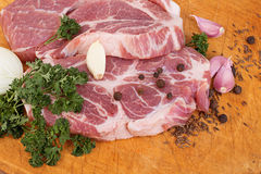 Fresh red meat with spices and parsley close-up on a wooden table. Stock Images