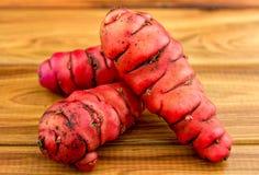 Fresh red new zealand yams (pink oca) on wood stock photo