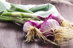 Fresh red onion bundle on wooden table background Royalty Free Stock Photography