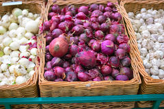 Fresh red onion in wicker tray on shelf in mall Royalty Free Stock Photo