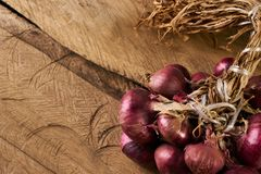 Fresh red onions on old rustic wooden table. A lot of onions on wooden table. Heap of onions on a old rustic wooden board. Fresh red Onion on wooden background Royalty Free Stock Photos
