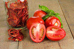 Fresh red paste tomatoes with basil and jar. Fresh red tomatoes and basil with jar of dried tomatoes stock image