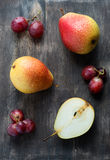 Fresh red pears and grapes on the dark wooden table Royalty Free Stock Images