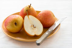 Fresh red pears on plate over light background Stock Image