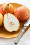 Fresh red pears on plate over light background Royalty Free Stock Photos