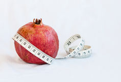 Fresh red Pomegranate fruit and measuring tape Royalty Free Stock Image