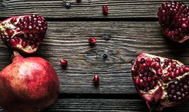 Fresh red pomegranate and grapefruit On a wooden background. Pomegranate in plate on wood background. Pomegranate on wood textured background. Overhead view Stock Images