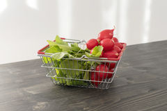 Fresh red radish in a basket on a wooden background Stock Photo