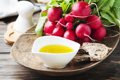 Fresh red radish with olive oil on the wooden table. Selective focus Royalty Free Stock Images