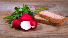 Fresh red radish parsley and bread on old wooden surface. Fresh red half radish parsley and bread on old wooden surface Stock Photos