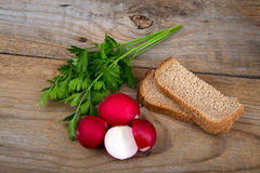 Fresh red radish parsley and bread on old wooden surface. Fresh red half radish parsley and bread on old wooden surface Royalty Free Stock Photo