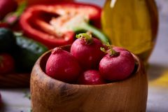 Fresh red radish in wooden bowl in front of plate with vegetables, selective focus. Fresh red radish in wooden bowl in front of plate with vegetables on wthite Royalty Free Stock Image