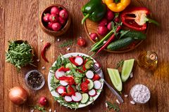 Fresh red radish in wooden bowl among plates with vegetables, herbs and spicies, top view, selective focus. Fresh red radish in wooden bowl among plates with Stock Photos