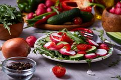 Fresh red radish in wooden bowl among plates with vegetables, herbs and spicies, top view, selective focus. Fresh red radish in wooden bowl among plates with Stock Photography