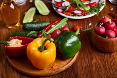 Fresh red radish in wooden bowl among plates with vegetables, herbs and spicies, top view, selective focus. Fresh red radish in wooden bowl among plates with Stock Photo