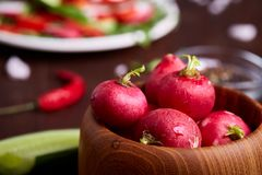 Fresh red radish in wooden bowl among plates with vegetables, herbs and spicies, top view, selective focus. Fresh red radish in wooden bowl among plates with Royalty Free Stock Images