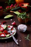 Fresh red radish in wooden bowl among plates with vegetables, herbs and spicies, top view, selective focus. Fresh red radish in wooden bowl among plates with Stock Images