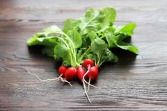 Fresh red radishes with green leaves on table. Fresh red radishes with green leaves on brown wooden table royalty free stock photo