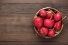 Bowl of fresh red radishes. Fresh red radishes in wooden bowl on the brown table with copy space Stock Photo