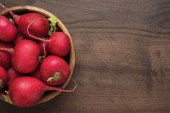 Bowl of red radishes. Fresh red radishes in wooden bowl on the brown table with copy space Stock Images