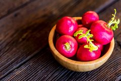 Fresh red radishes in wooden bowl close. Close up fresh bright red redishes in wooden bowl on dark wooden surface. Healthy diet concept, selective focus Royalty Free Stock Images