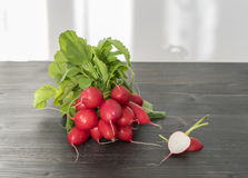 Fresh red radishes on a wooden table in the kitchen. Bunch of fresh red radishes on a wooden table in the kitchen Royalty Free Stock Photo