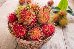Fresh red rambutan sweet delicious fruit in basket on wood table. Tropical fruit tree, native to South - East Asia , cultivated in. Many countries in the region Stock Image