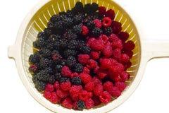 Fresh raspberries and blackberries in sieve. Fresh red raspberries and blackberries in sieve, selective focus Royalty Free Stock Photo