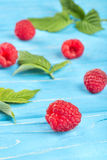 Fresh red raspberries. Scattered fresh red raspberries with leaves on a blue table Royalty Free Stock Images